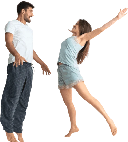 happy man and woman jumping in bed